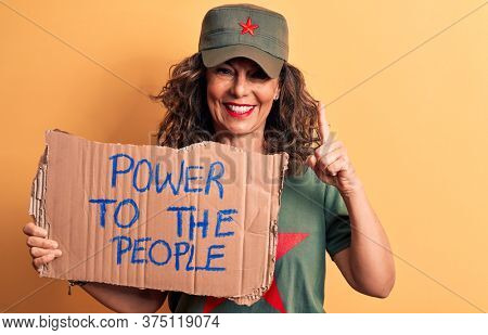 Middle age brunette communist woman holding banner with power to the people message smiling with an idea or question pointing finger with happy face, number one