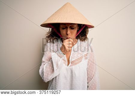 Middle age brunette woman wearing asian traditional conical hat over white background feeling unwell and coughing as symptom for cold or bronchitis. Health care concept.