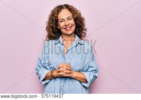 Middle age beautiful woman wearing casual denim shirt standing over pink background with hands together and crossed fingers smiling relaxed and cheerful. Success and optimistic