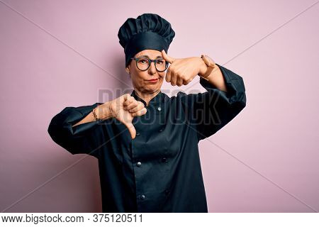 Middle age brunette chef woman wearing cooker uniform and hat over isolated pink background Doing thumbs up and down, disagreement and agreement expression. Crazy conflict