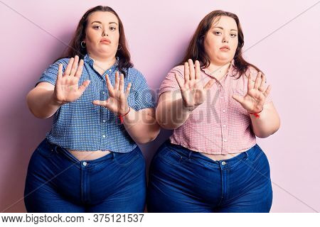 Young plus size twins wearing casual clothes moving away hands palms showing refusal and denial with afraid and disgusting expression. stop and forbidden.
