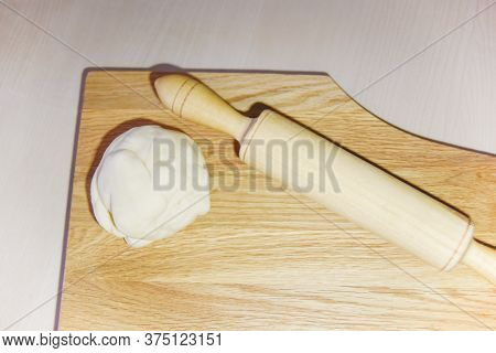 Selective Focus At The Dough And Roller At The Wooden Chopping Board