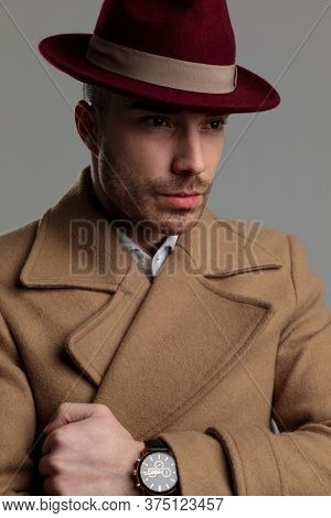 young fashion model wearing hat and long coat, looking to side and fixing coat on grey background
