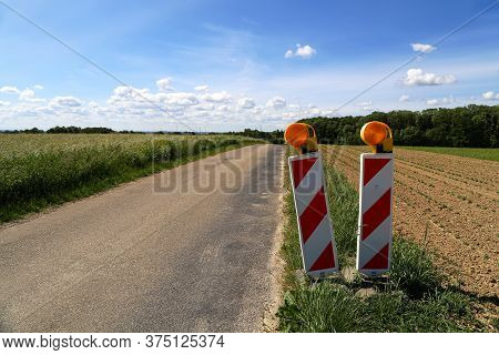 Rural Landscape With A Field Road And Road Marking Pole With Reflectors