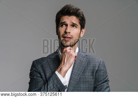Photo of perplexed young businessman in jacket posing and looking aside isolated over grey wall