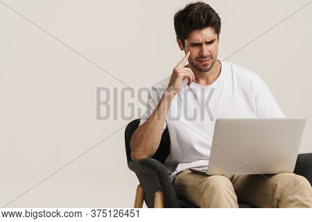 Portrait of unshaven perplexed man working with laptop while sitting on armchair isolated over white background