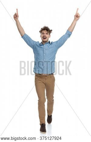 enthusiastic casual man pointing fingers in the air and celebrating victory, walking isolated on white background, full body