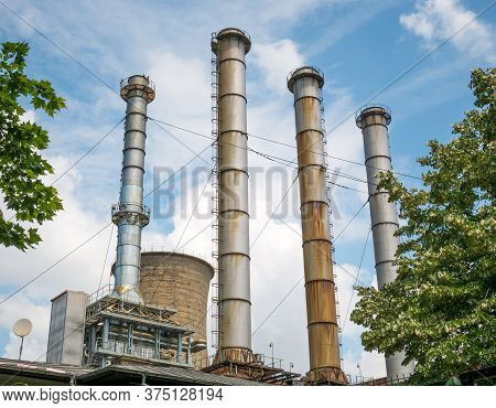 Chimneys And Cooling Towers Of A Thermal Power Plant Against Blue Sky. Power Station In Bucharest.