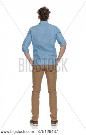 back view of young casual guy holding hands in pockets, standing isolated on white background, full body