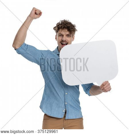 enthusiastic guy holding speech bubble, holding arms up and celebrating victory, standing isolated on white background, portrait