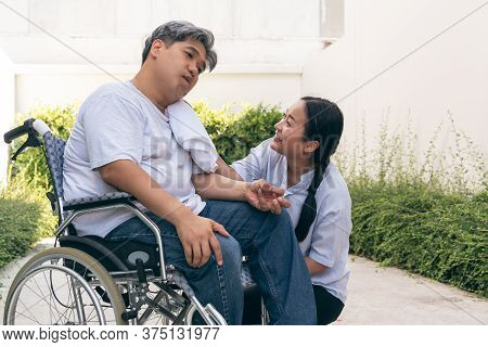 The Wife Is Taking Care Of The Husband Sitting On Wheelchair,  Who Is Suffering From Neurological Di