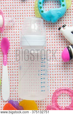 Baby Accessories On Pink Pattern Background On Table. Spoon And Empty Bottle For Milk For Feeding. T