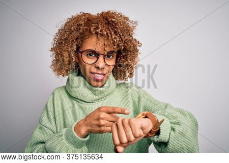 Young beautiful african american woman wearing turtleneck sweater and glasses In hurry pointing to watch time, impatience, upset and angry for deadline delay