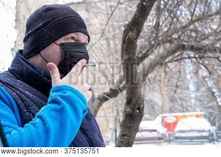Smoking. Closeup Man With Mask During Covid-19 Pandemic Smoking A Cigarette At The Street. A Man In