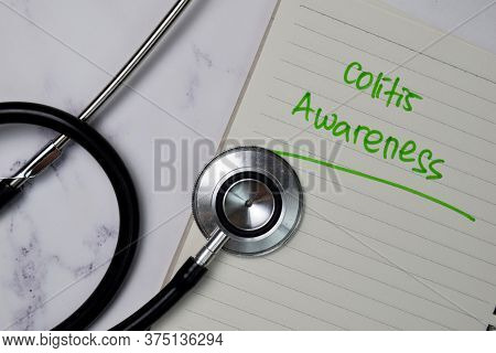 Colitis Awareness Write On A Book Isolated Wooden Table.