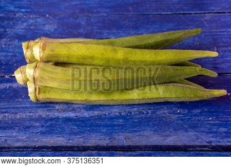 Organic Okra Or Lady Finger Vegetable Isolated On Wooden Background