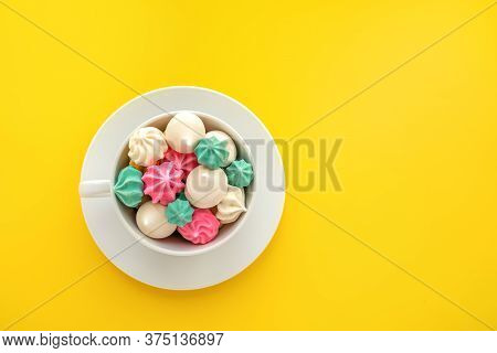 Colourful Meringue In A Coffee Cup On Yellow Background With Space For Text. Sweet Meringues Flat La