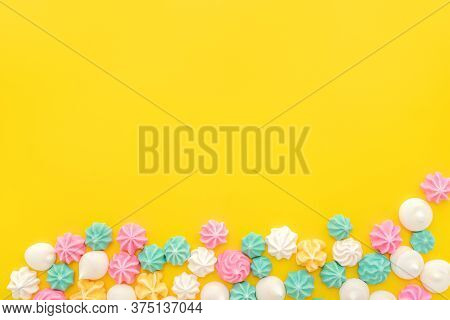 Colourful Meringue In Various Star Shapes On Yellow Background With Space For Text. Sweet Meringues
