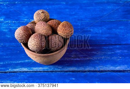 Lychee Or Litchi Fruits In A Clay Bowl Isolated On Wooden Background With Copy Space For Texts Writi