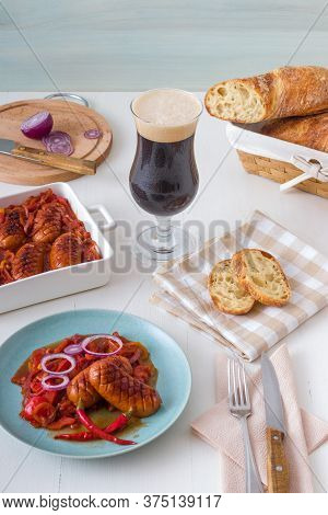 The Plate With Portion Of Baked Sausages In Dark Beer With Red Onion, Red And Yellow Paprika, Red Ho