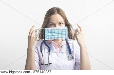 Female Doctor With Stethoscope Putting A Facial Mask On Standing Over White Background And Looking A