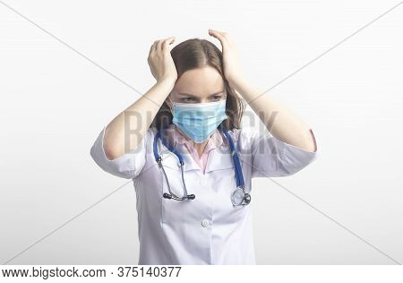 Confused Stressed Tired Young Caucasian Doctor In Protective Facial Mask Isolated On White Backgroun