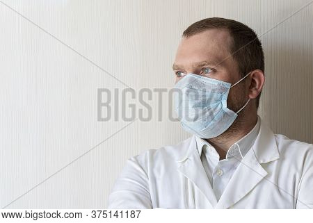 A Serious Young Male Doctor In A Medical Mask With A Gaze. Health