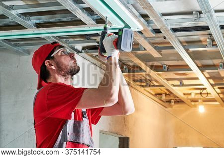 Gypsum plasterboard work. Drywall construction at home. Contractor worker installing metal frame on ceiling