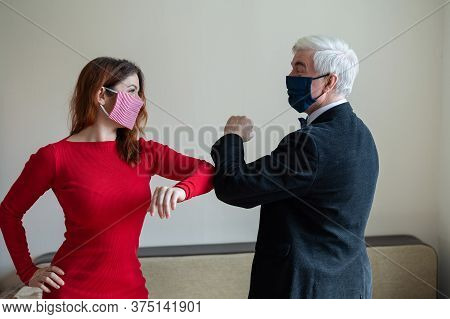 A Mature Gray-haired Man In A Suit And A Red-haired Woman In A Red Dress Wearing In Medical Masks Ma