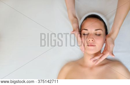 Spa Procedure Of Face Massage. Top View. Beautiful Young Woman Lying On Back. Masseur /therapist Mas