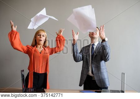 A Business Woman And Man Throwing Papers Up, At Wooden Office Desk