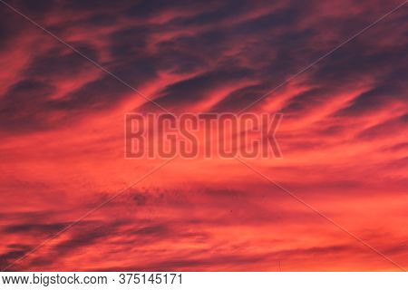 Dark Orange Clouds At Sunset. Picturesque Clouds In The Sky Backlit By The Sun.