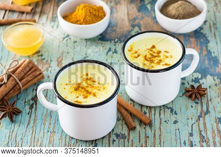 Detox Drink. Golden Milk With Turmeric And Cinnamon In Mugs On A Wooden Table. Rustic Style. Close-u