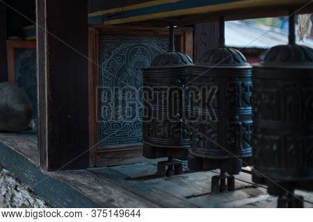 Close Up Of Buddhist Prayer Wheels With Sanskrit Mantra And Buddha Painting