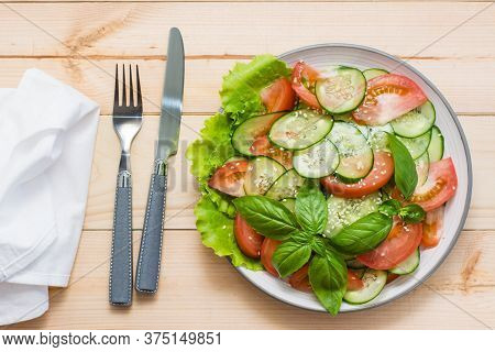 Traditional Salad Of Slices Of Cucumber, Tomatoes And Sesame Seeds On A Plate And Cutlery On A Woode