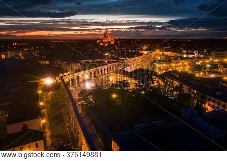 Segovia Cathedral and aqueduct aerial view at night in Spain.
