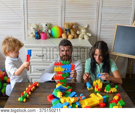 Young Family Spends Time In Playroom. Parents And Son