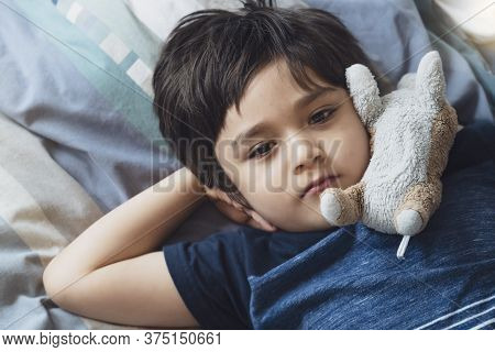 Top View Kid Lying Down On Bed And Looking Up With Thinking Face, Candid Young Boy Laying Down With