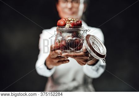 Female Chef Holds A Glass With Fresh Red Juicy Berries. Close Up View On A Wet Glass With Ripe Straw