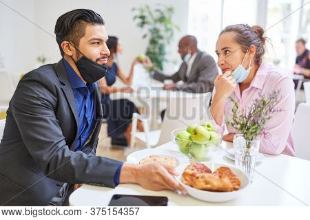 Two young businesspeople as a couple flirting in the cafeteria with a face mask on their chin