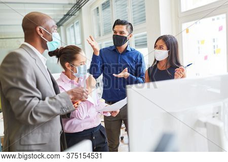 Start-up team of an internet agency with face mask discusses the development of a website