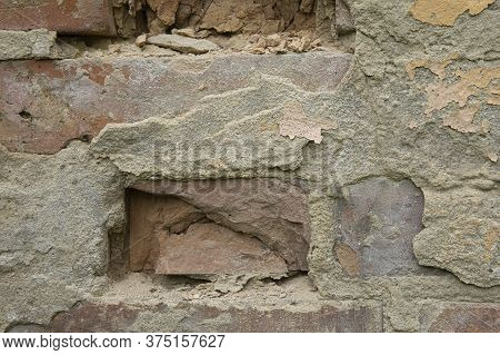 Close Up Of Damaged Wall With Old Bricks And Grey Plaster