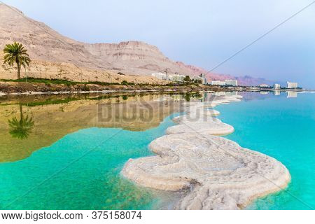 Israel. Concept of ecological, medical and photo tourism. Early morning at the resorts of the Dead Sea. Azure sea water is full of healing salts. Small islets and path of salt in the water