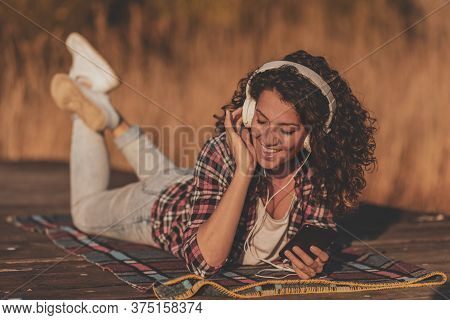 Woman Wearing Headset Lying On The Lake Docks, Using A Smart Phone, Choosing A Song From A Playlist,