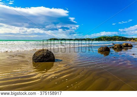 Moeraki's huge round boulders on a sandy beach. The Pacific ocean tide begins in  New Zealand. The sun's rays are reflected in the ocean water. The concept of ecological, exotic and phototourism