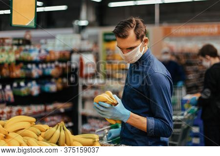 Customer In Protective Gloves Choosing Bananas In A Supermarket