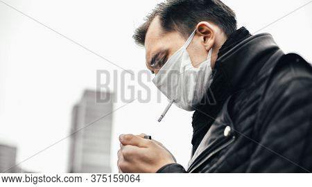 Serious Man In A Protective Mask Lighting His Cigarette