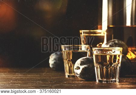 Slivovica - Plum Brandy Or Plum Vodka, Hard Liquor, Strong Drink In Glasses On Old Wooden Table, Fre