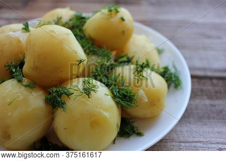 New Potatoes With Dill On Old Wooden Board Table. Close-up Of Whole Boiled Potatoes On The White Pla