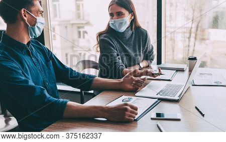 Employees In Protective Masks Work In The Office.
